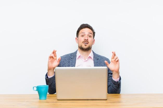 Jovem empresário bonitão cruzando os dedos ansiosamente e esperando a boa sorte com um olhar preocupado Foto Premium