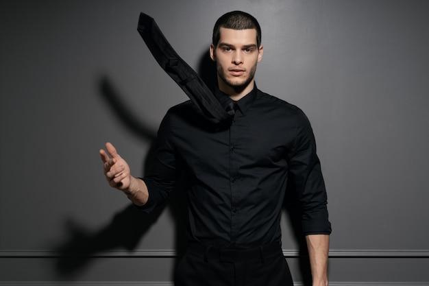 Jovem empresário bonitão na camisa preta Foto gratuita