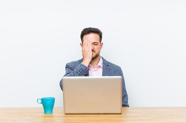 Jovem empresário bonitão olhando sonolento, entediado e bocejando, com dor de cabeça e uma mão cobrindo metade do rosto Foto Premium