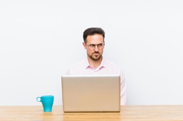 Jovem empresário bonitão se sentindo triste, chateado ou com raiva e olhando para o lado com uma atitude negativa, franzindo a testa em desacordo Foto Premium