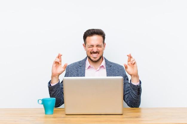 Jovem empresário bonitão sorrindo e cruzando ansiosamente os dois dedos Foto Premium