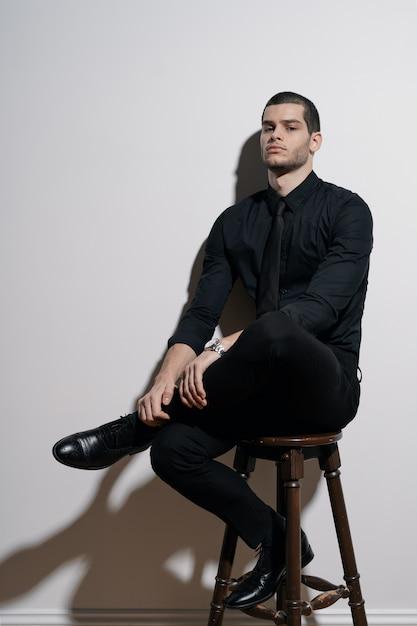 Jovem empresário bonito de camisa preta e terno preto Foto gratuita