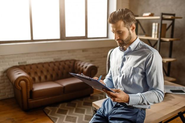 Jovem empresário bonito sentar na mesa e olhar para os papéis em seu próprio escritório. ele leu documentos. jovem sexy pensativo trabalhando, luz do dia. Foto Premium