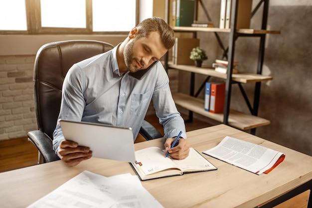 Jovem empresário bonito trabalhar em seu próprio escritório. ele se senta à mesa e fala ao telefone. também cara escrevendo documentos. ocupado. tempo de trabalho. luz do dia. Foto Premium