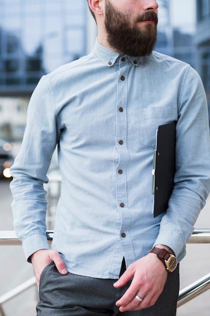 Jovem empresário com as mãos no bolso, segurando a prancheta Foto gratuita