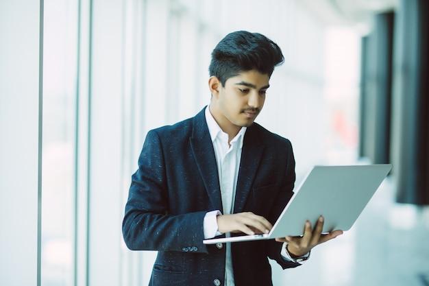 Jovem empresário com computador portátil trabalhando no escritório Foto gratuita