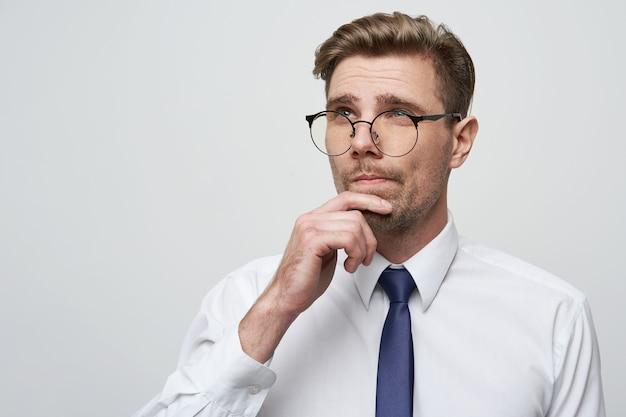 Jovem empresário com expressão séria no rosto pensando na pergunta Foto gratuita