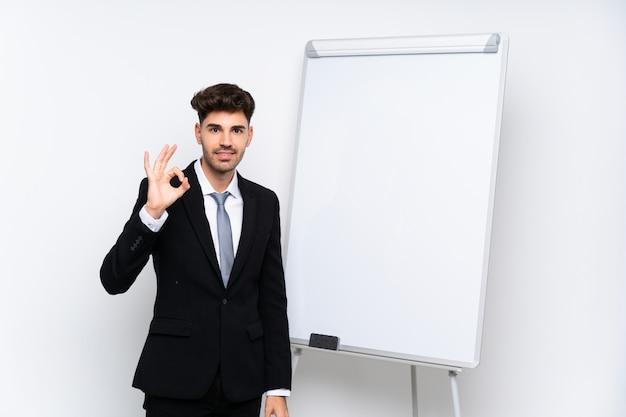 Jovem empresário, dando uma apresentação no quadro branco, mostrando sinal de ok com os dedos Foto Premium