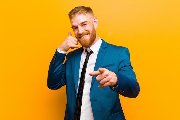 Jovem empresário de cabeça vermelha, sorrindo alegremente e apontando para a câmera enquanto faz uma ligação, gesto mais tarde, falando na parede do telefone laranja Foto Premium