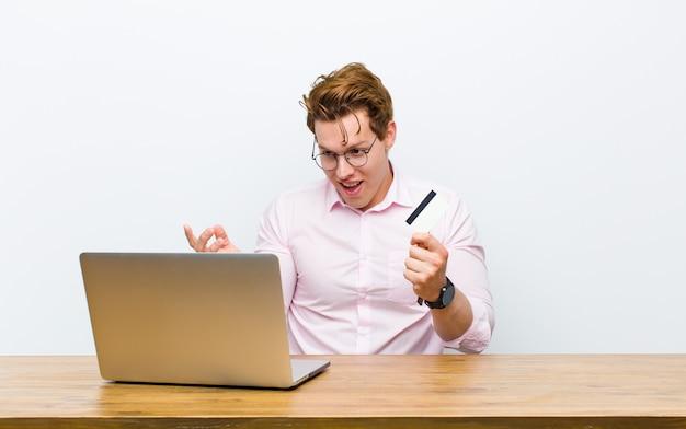 Jovem empresário de cabeça vermelha, trabalhando em sua mesa com cartão de crédito Foto Premium