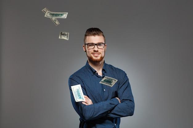 Jovem empresário de sucesso posando entre dinheiro caindo sobre parede escura. Foto gratuita