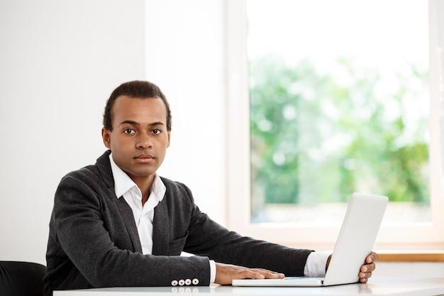 Jovem empresário de sucesso sentado no local de trabalho com computador portátil Foto gratuita