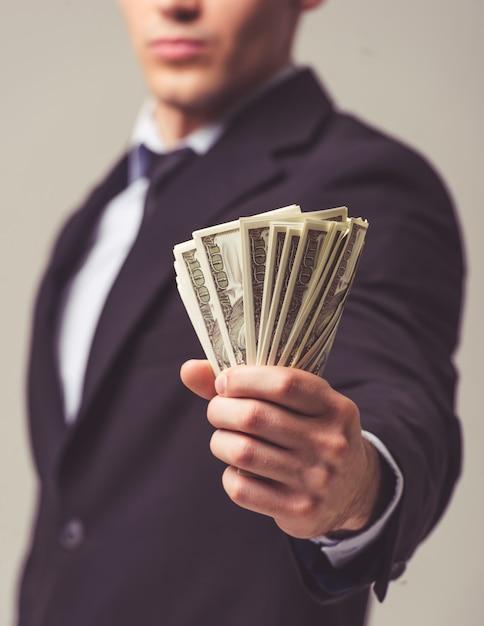 Jovem empresário de terno segurando dinheiro Foto Premium