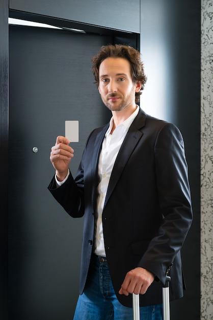 Jovem empresário em pé com um cartão-chave na frente da porta de um quarto em um hotel Foto Premium