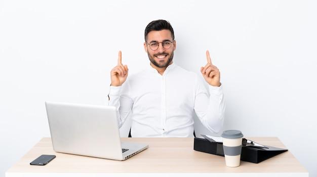 Jovem empresário em um local de trabalho apontando para cima uma ótima idéia Foto Premium