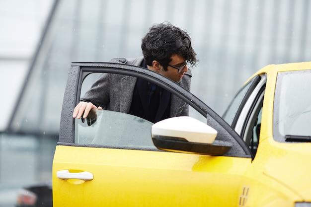 Jovem empresário entrar no táxi Foto gratuita