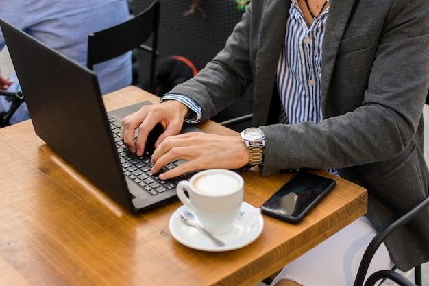 Jovem empresário está trabalhando em um bar no terraço com seu laptop e smartphone. fechar-se Foto Premium