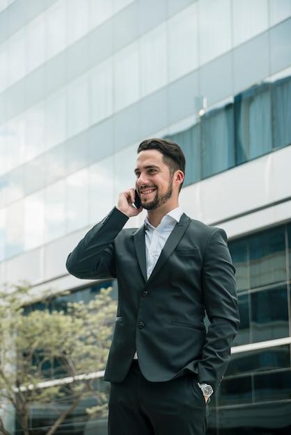 Jovem empresário falando no celular com a mão no bolso Foto gratuita