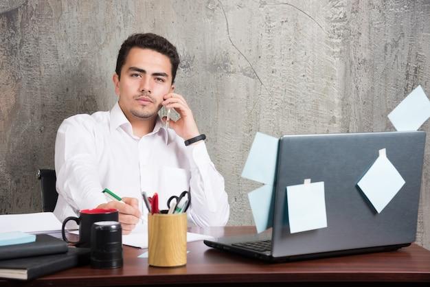 Jovem empresário falando sobre assuntos sérios na mesa do escritório. Foto gratuita
