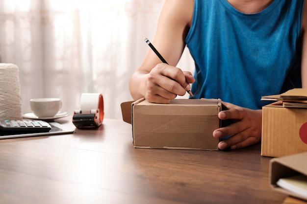 Jovem empresário inicialização escrever o endereço na caixa de papelão em casa Foto Premium