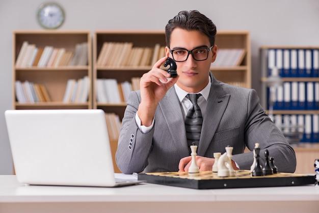 Jovem empresário jogando xadrez no escritório Foto Premium
