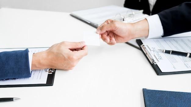 Jovem empresário na entrevista de contratação no escritório, reunião no lobby do escritório, mudança de cartões de visita Foto Premium