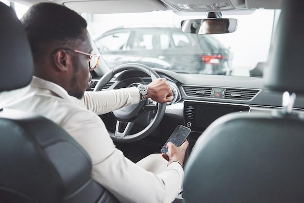 Jovem empresário negro test drive novo carro. homem rico afro-americano. Foto gratuita