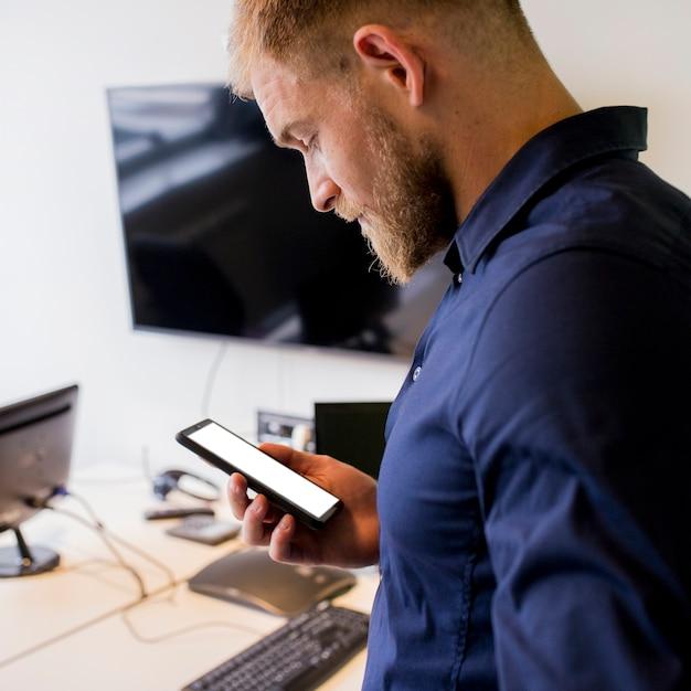 Jovem empresário, olhando para o celular de tela em branco Foto gratuita