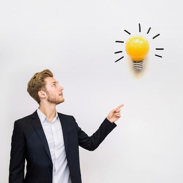 Jovem empresário, olhando para uma lâmpada Foto gratuita