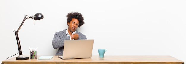 Jovem empresário preto olhando arrogante, bem sucedido, positivo e orgulhoso, apontando para si mesmo em uma mesa Foto Premium