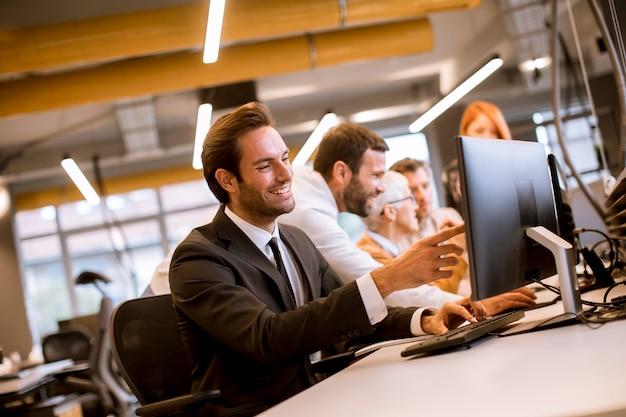 Jovem empresário profissional usa um laptop para trabalhar no escritório Foto Premium