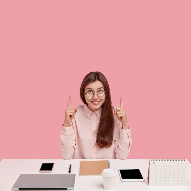 Jovem empresário próspero de sucesso com olhar alegre, aponta os dois dedos indicadores para o teto, usa camisa elegante e óculos Foto gratuita