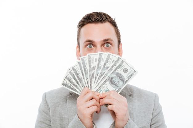 Jovem empresário segurando o dinheiro cobrindo o rosto. Foto gratuita