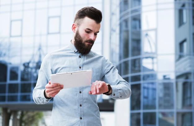 Jovem empresário segurando o tablet digital na mão, verificando o tempo Foto gratuita