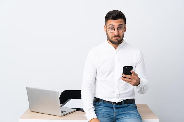 Jovem empresário segurando um telefone móvel triste Foto Premium