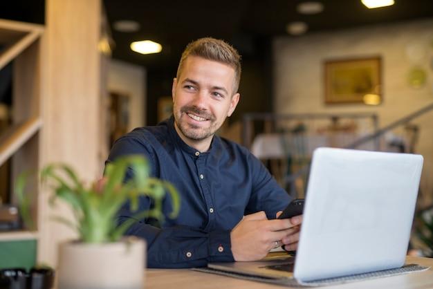Jovem empresário sentado em um café bar aconchegante, usando um laptop e olhando para o lado Foto gratuita