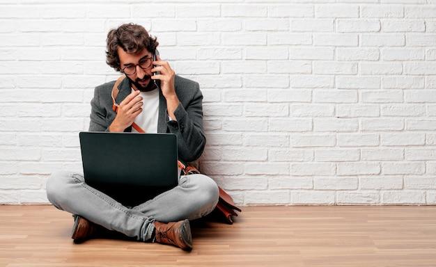 Jovem empresário sentado no chão com um laptop Foto Premium