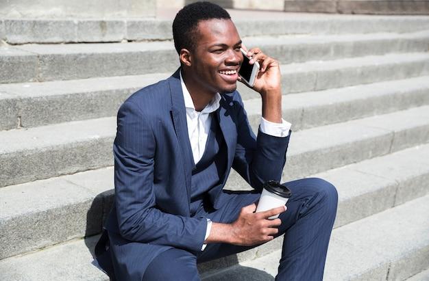 Jovem empresário sentado nos degraus, segurando o copo descartável na mão Foto gratuita
