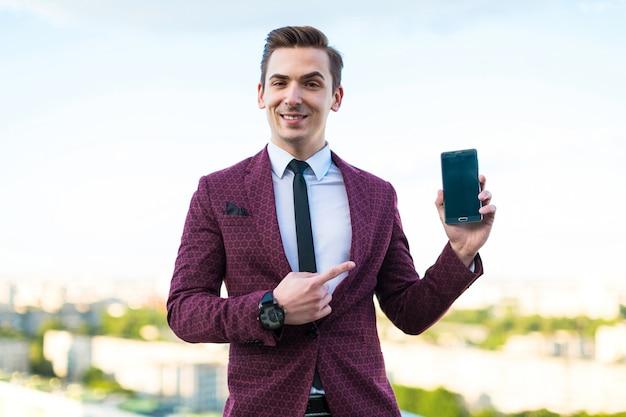 Jovem empresário sério de terno vermelho e camisa com gravata fica no telhado e mostra o telefone vazio Foto Premium