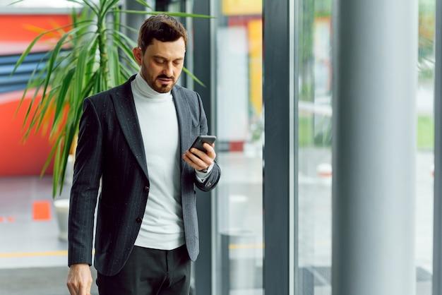 Jovem empresário sorridente ligando para o telefone no escritório. Foto Premium