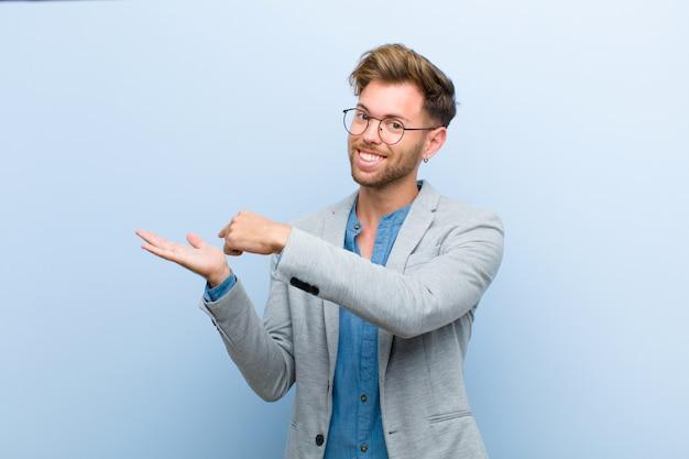 Jovem empresário sorrindo alegremente e apontando para copiar o espaço na palma da mão, mostrando ou anunciando um objeto contra azul Foto Premium