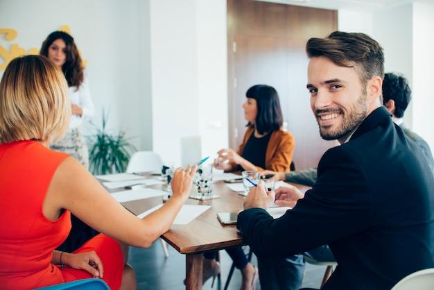 Jovem empresário sorrindo para a reunião Foto gratuita