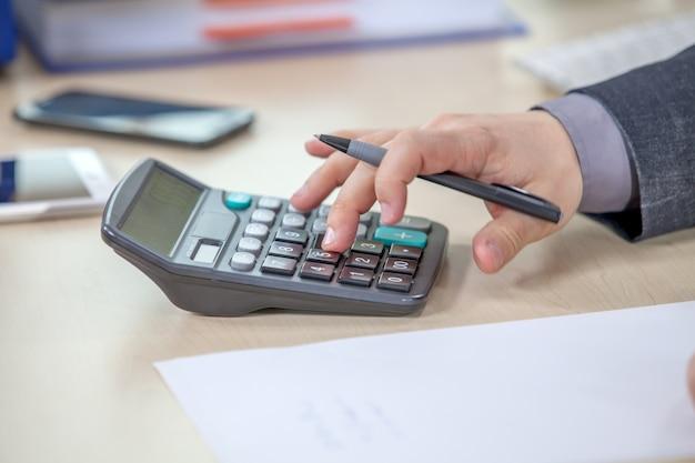 Jovem empresário trabalhando em seu escritório e calculando números Foto gratuita