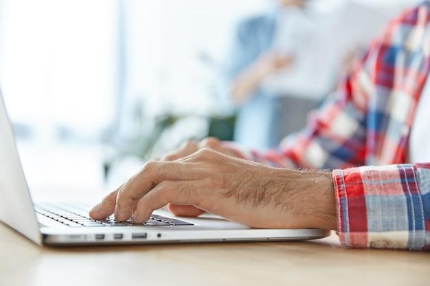 Jovem empresário usa laptop moderno na mesa do escritório, digita informações e prepara relatório financeiro Foto gratuita