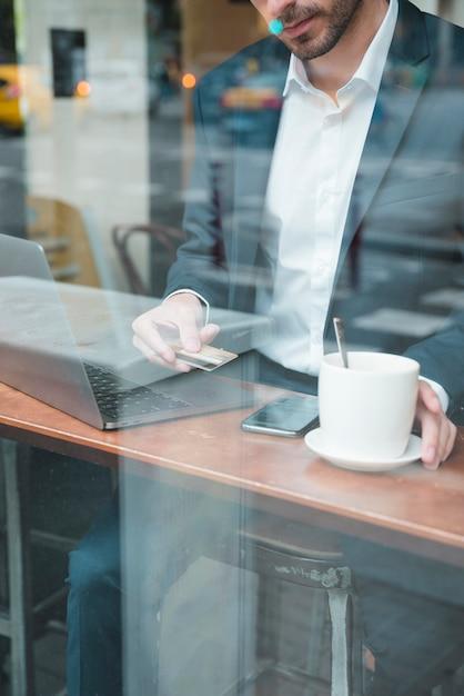 Jovem empresário usando cartão de crédito para pagar a conta no café Foto gratuita