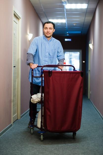 Jovem empurrando um carrinho de limpeza carregado com toalhas limpas, lavanderia e equipamentos de limpeza em um hotel, enquanto ele atende os quartos Foto Premium