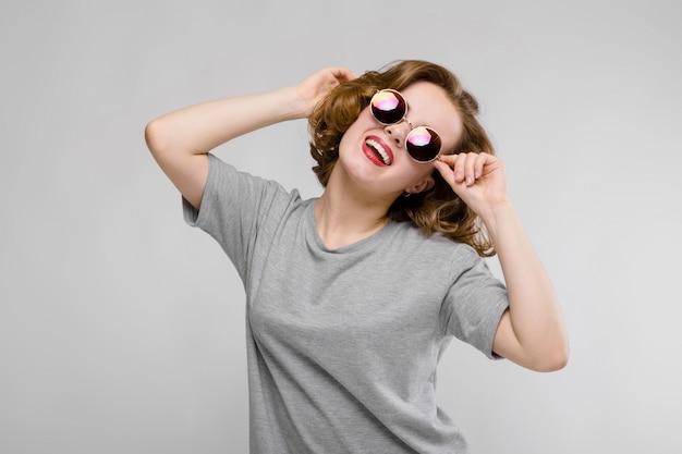 Jovem encantadora em uma camiseta cinza sobre um fundo cinza. menina alegre em copos redondos Foto Premium