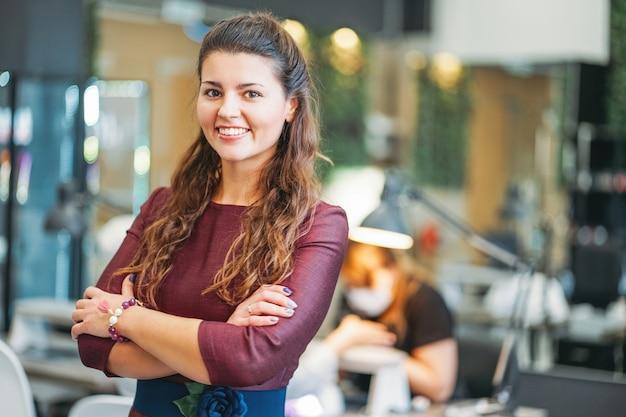Jovem encantadora mulher sorridente proprietário da barra de unha do salão de beleza, conceito de própria empresa Foto Premium