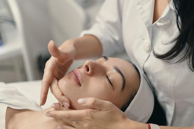 Jovem encontra-se com os olhos fechados, procedimento de tomada de cosmetologista Foto gratuita