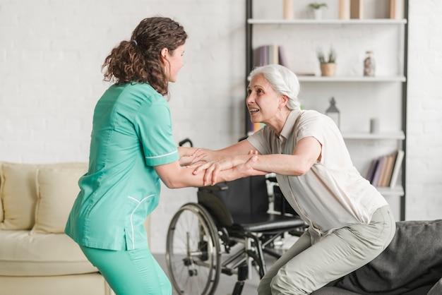 Jovem, enfermeira, ajudando, incapacitado, mulher sênior Foto gratuita